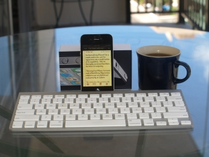 An iPhone showing the text of a note about itself,  with a wireless Bluetooth keyboard and a coffee mug, on a glass table.