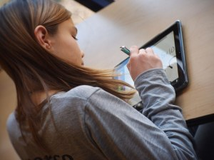Student using iPad in school. Image via Flickr by Flickingerbrad.