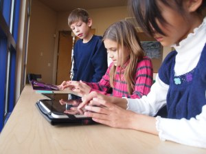Students using iPads in school. Image via Flickr by flickingerbrad.